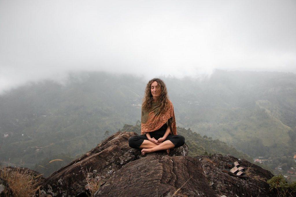Une femme fait une méditation de pleine conscience en position de demi lotus dans les montagnes